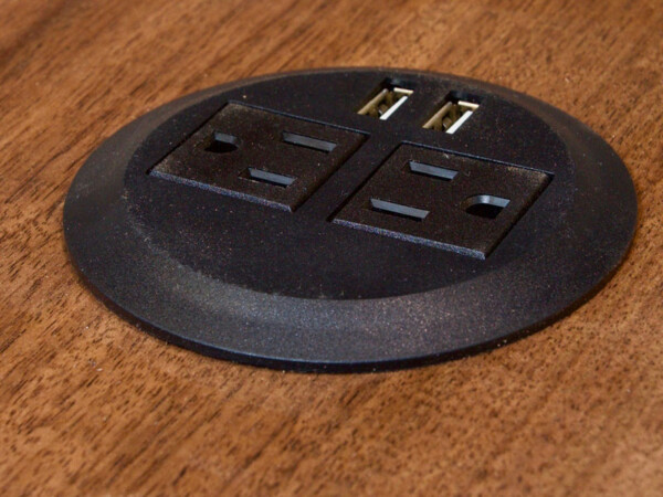 Closeup of outlet & USB ports as part of a desk