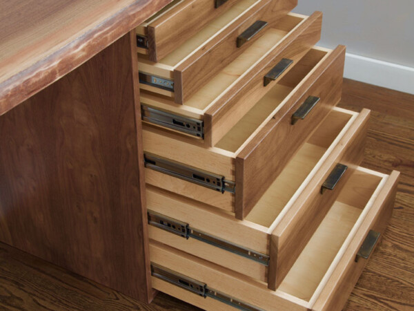 6 drawers of increasing size partly opened on a wood desk